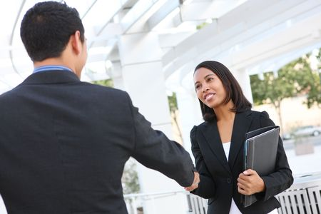 Attractive man and woman business team shaking hands at office building photo