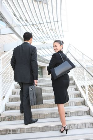 working at office: Attractive man and woman business team on stairs at office building Stock Photo
