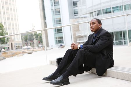 african business man: A handsome African Business Man Sitting at Office Building