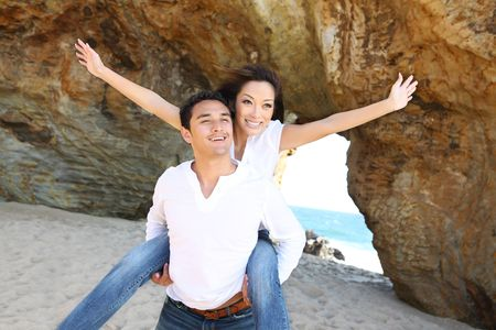 piggyback: An attractive couple having fun at the beach