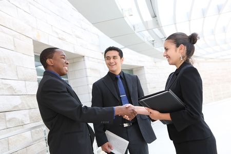 african american handshake: An attractive, diverse business team meeting as a group