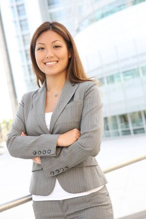 young asian girl: A young, pretty asian business woman at office building Stock Photo