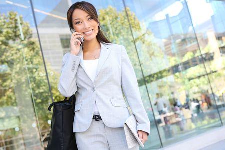 オフィスでの携帯電話で美しい若いアジア ビジネス女性