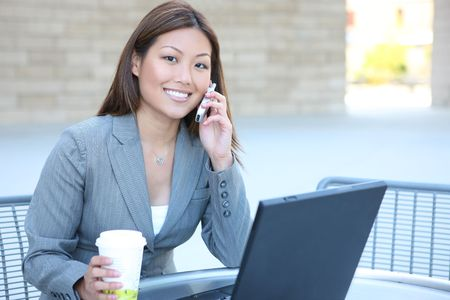 A pretty asian business woman working on laptop computer photo