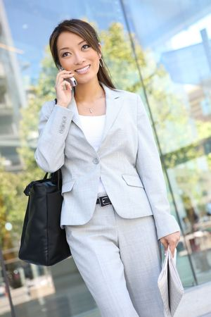 A beautiful young asian business woman on the cell phone at office photo