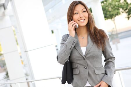 phone business: A beautiful asian business woman on cell phone at office building