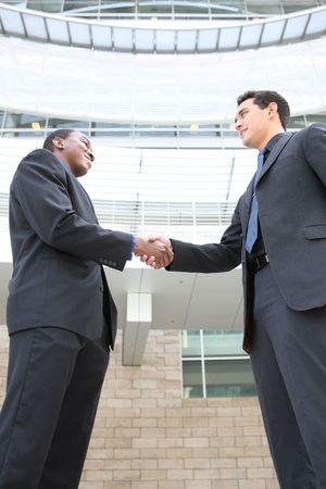 An attractive, diverse business man team shaking hands (Focus on Hands)