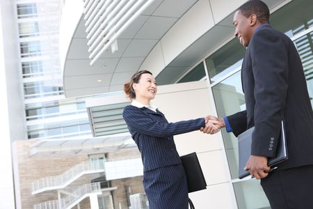 filipino people: An attractive team of diverse business people shaking hands Stock Photo