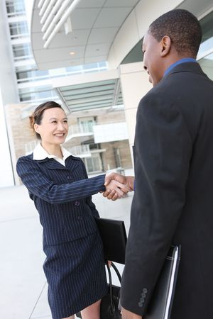 business transaction: An attractive team of diverse business people shaking hands Stock Photo