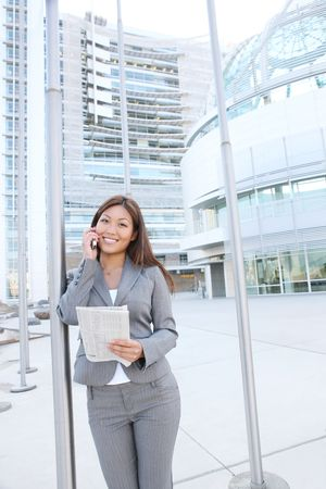 A beautiful asian business woman on cell phone at office building photo