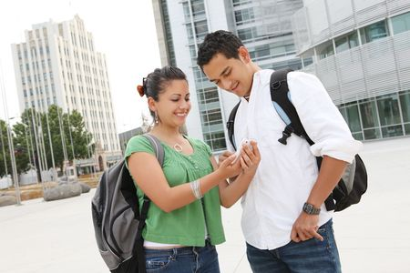 school campus: Attractive students at college texting with mobile phone Stock Photo