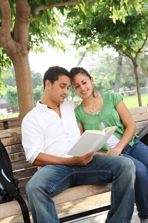 Attractive students at college sitting on bench photo