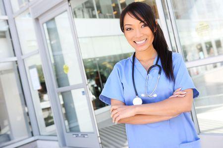 A young pretty asian nurse outside the hospital photo