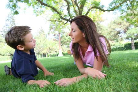 mom son: A mother and son talking while relaxing in the park