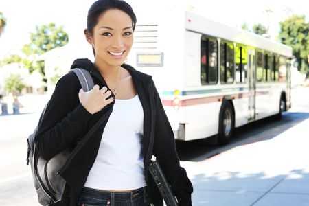 A cute young asian teenager getting off the bus to go to college