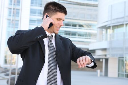 looking at watch: A handsome business man looking at watch and talking on cell phone Stock Photo