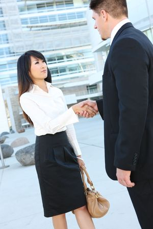 An attractive diverse business team shaking hands at office building photo