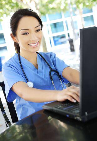 female nurse: A young pretty asian nurse outside the hospital on laptop computer Stock Photo