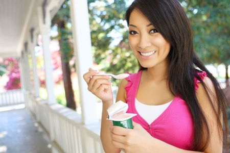 A pretty asian woman at home eating yogurt