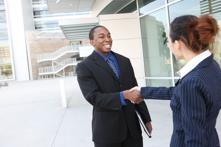 An attractive team of diverse business people shaking hands Фото со стока