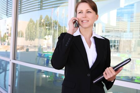 A pretty business woman at the office building on her cell phone photo