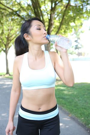 A young pretty asian woman drinking water after Exercise Stock Photo