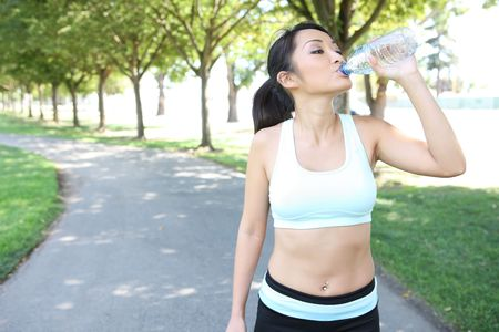 A young pretty asian woman drinking water after Exercise photo