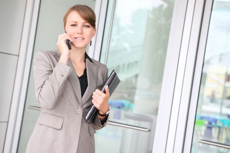 A pretty business woman at the office building on her cell phone Stock Photo - 3492458