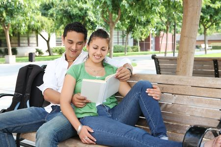 Attractive students at college sitting on bench reading photo