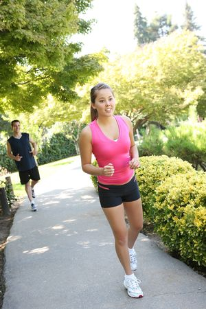 An attractive man and woman couple jogging in the park photo