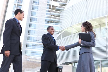 A diverse ethnic business team shaking hands at office building photo