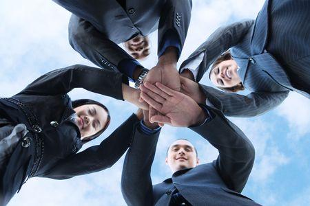 一緒に手で多様なビジネスの男性と女性のチーム、