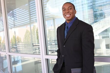 A handsome african american business man in front of company photo