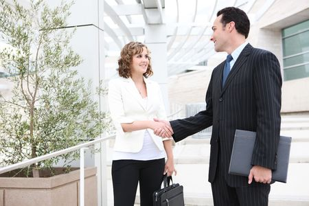 meet and greet: An attractive man and woman business team shaking hands at office Stock Photo
