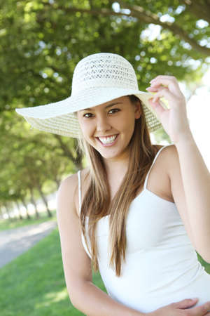 Happy young female woman at the park wearing hat photo