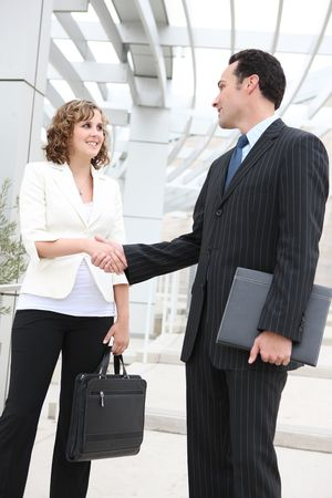 welcome people: An attractive man and woman business team shaking hands at office Stock Photo