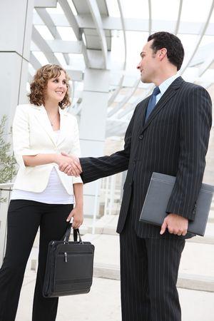 Een aantrekkelijke man en vrouw business team handen schudden bij het kantoor