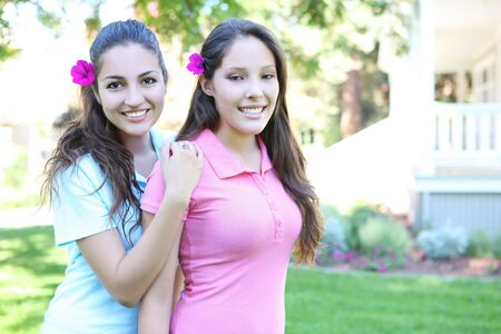 Two attractive hispanic sisters smiling outside home Stock Photo - 3599344
