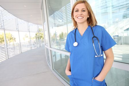 A pretty young woman nurse outside hospital building