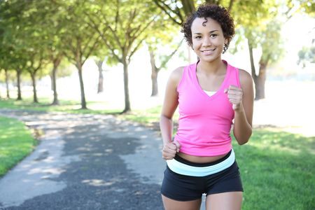 healthy path: A young pretty african american woman jogging in the park