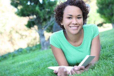 A pretty african american woman reading a book at the park photo