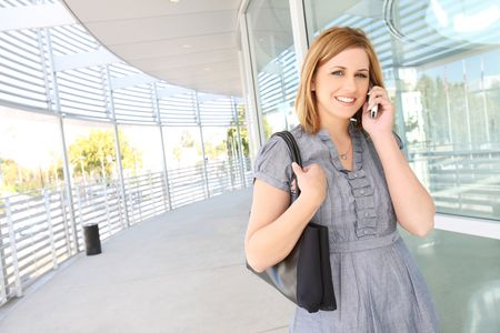 A pretty, young business woman at office building on phone photo