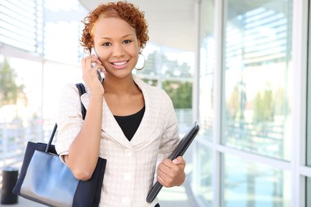 A pretty african american business woman on the cell phone at office Stock Photo - 3655374