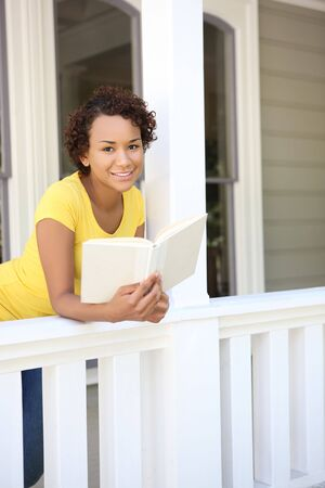 A pretty, young african woman on porch reading a book photo