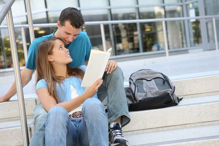 Attractive Man and Woman couple at School Library on Stairs Reading photo