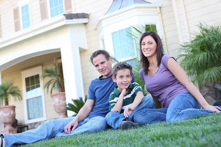 case colorate: Una famiglia felice di divertimento all'aria aperta di fronte a casa loro
