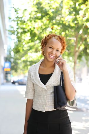 A pretty african american business woman on the cell phone walking to work Stock Photo - 3784301