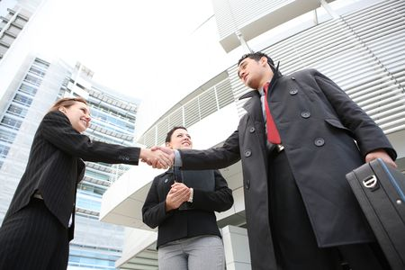 Attractive man and woman business team shaking hands photo