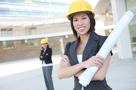 asian architect: Two pretty women working as architects on a construction site
