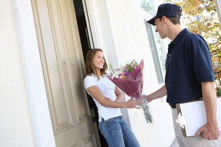 door to door delivery: A delivery man giving flowers to pretty woman at home Stock